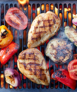 Close up of chicken breasts and veggies on the grill