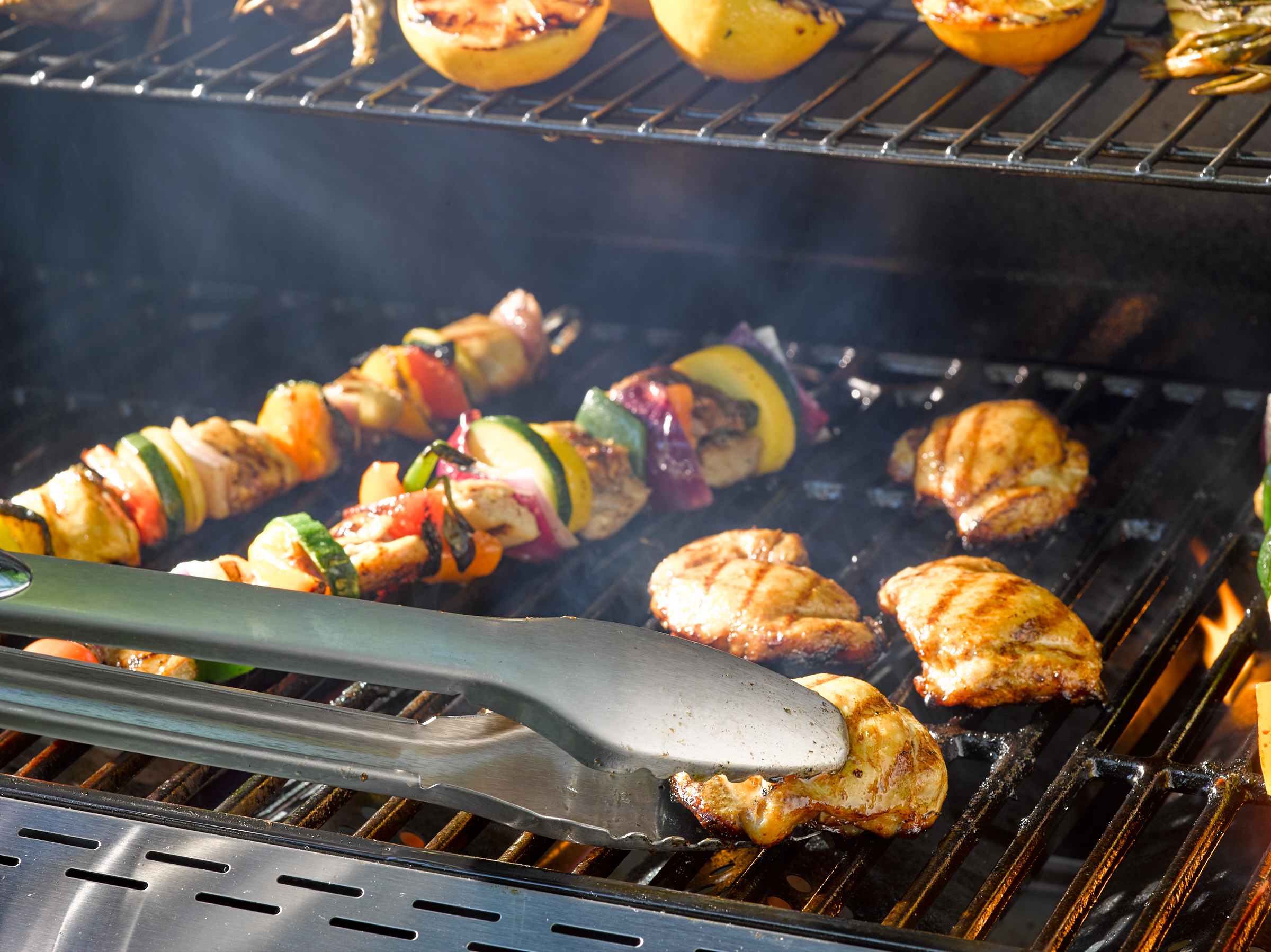 Close up image of flipping chicken breast on grill with large metal tongs.