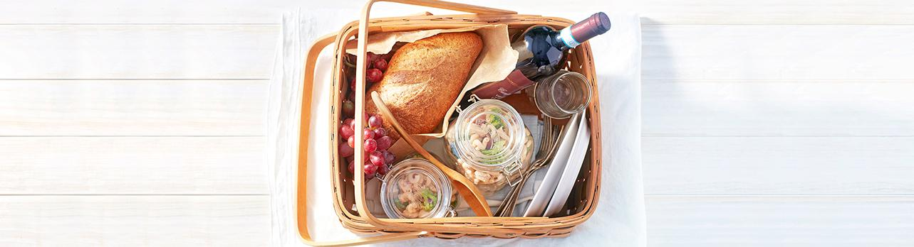 Packed picnic basket with chicken salad, bread and wine.
