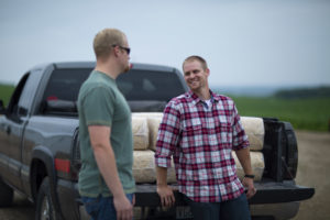 Two farmers chatting near a truck filled with hay.