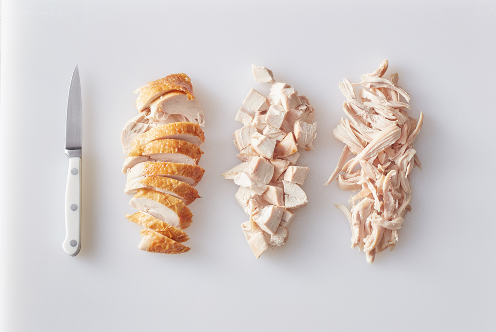 Cooked chicken cut up three different ways, sliced, cubed, and pulled.