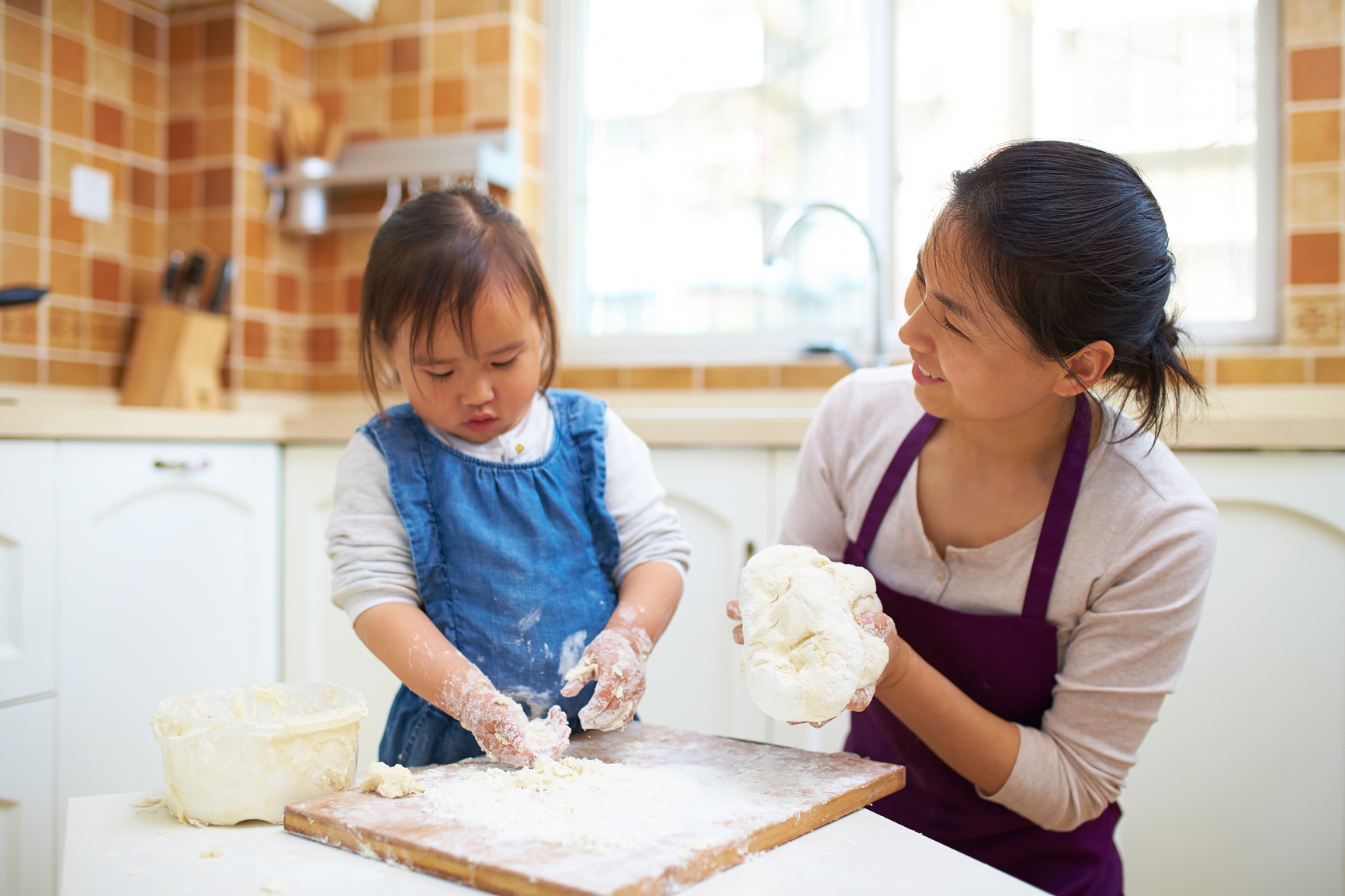 Mother and daughter making dough together in a kitchen and smiling.