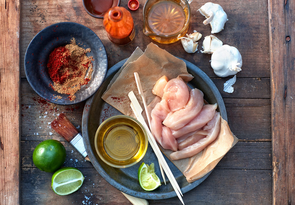 All of the ingredients for making chicken skewers on a grill laid out on a wooden board.